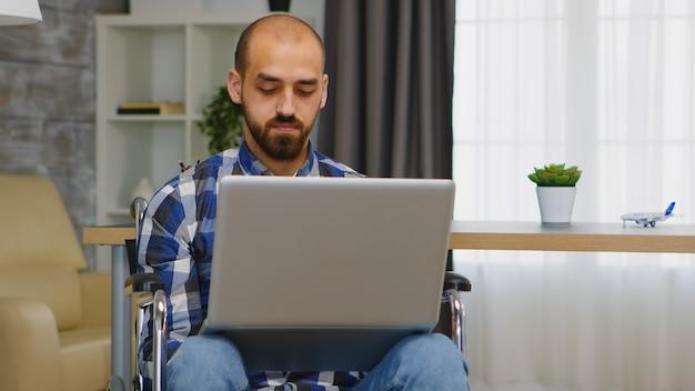 Zakenman in rolstoel die op afstand werkt vanuit huis op laptop.
