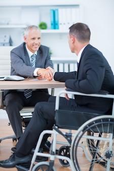 Zakenman in rolstoel het schudden van handen met collega