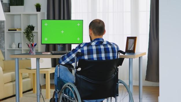 Zakenman in rolstoel voor computer met groen scherm.