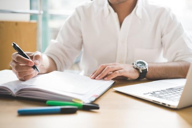 Zakenman in wit overhemd die aan bureaulijst werken