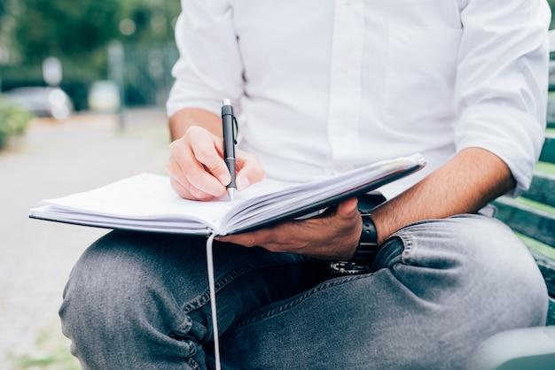 Zakenman in wit overhemd die met laptop zitting aan een bank in een park werken