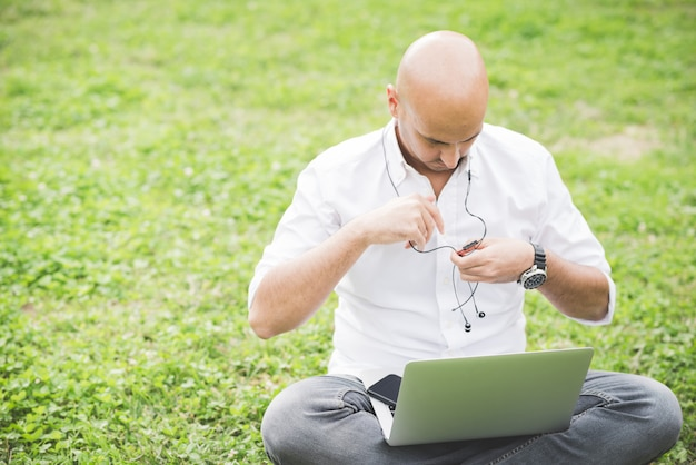 Zakenman in wit overhemd die met laptop zitting aan het gras in een park werken