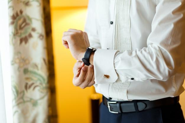 Zakenman in wit overhemd, zwarte lederen riem en manchetknopen die zijn dure horloge dragen