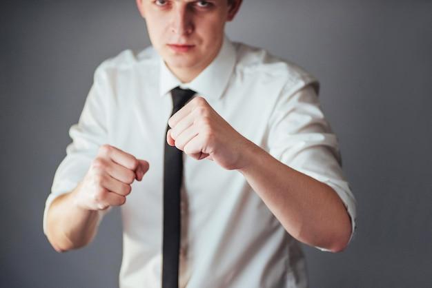Zakenman in zakelijke kleding boksen tegen een donkere achtergrond