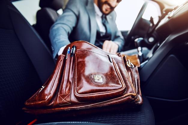 Zakenman in zijn auto zitten en iets uit zijn koffer halen. selectieve aandacht voor aktetas.