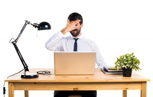Zakenman in zijn kantoor bedekt zijn gezicht