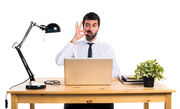 Zakenman in zijn kantoor maakt stilte gebaar