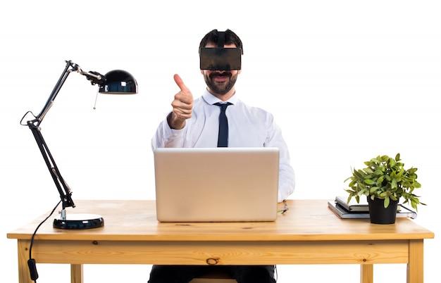 Zakenman in zijn kantoor met behulp van vr glazen met duim omhoog