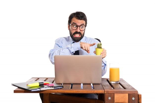 Zakenman in zijn kantoor met cactus