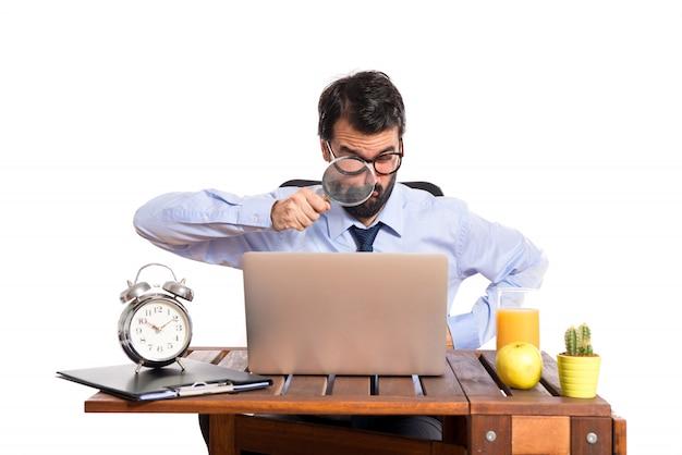 Zakenman in zijn kantoor met vergrootglas