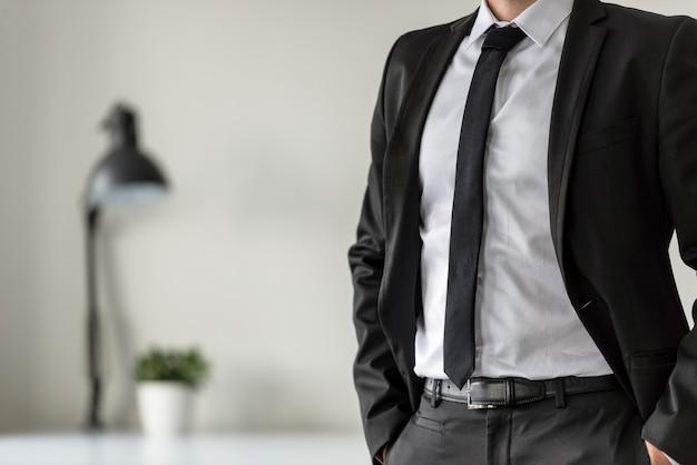 Zakenman in zijn kantoor met zijn handen in de zakken van zijn pak