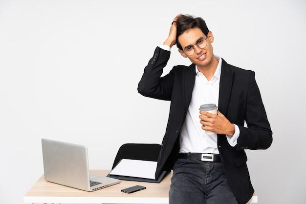 Zakenman in zijn kantoor over geïsoleerde witte muur lachen