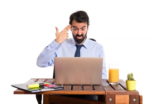 Zakenman in zijn kantoor zelfmoord gebaar maken