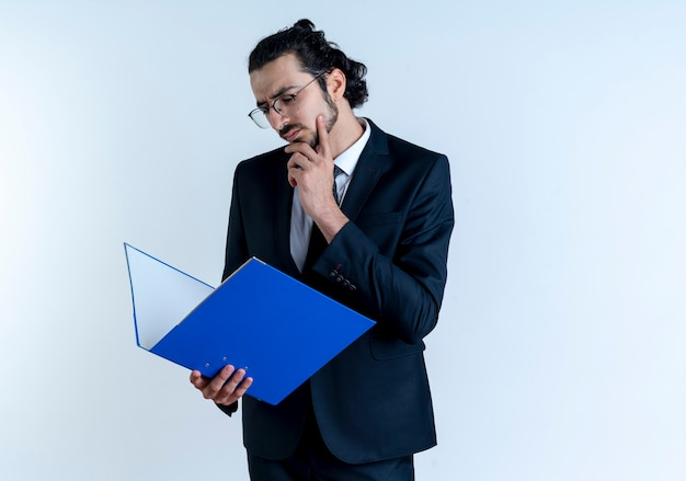 Zakenman in zwart pak en bril bedrijf map, kijken verbaasd staande over witte muur