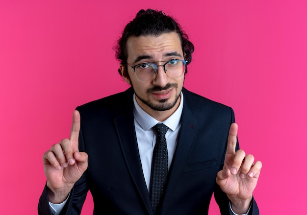 Zakenman in zwart pak en bril die naar voren kijken en wijsvingers tonen die zich over roze muur bevinden