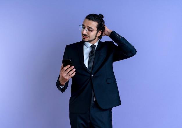 Zakenman in zwart pak en bril kijken naar scherm van zijn mobiele telefoon verward twijfels krabben zijn hoofd staande over blauwe muur