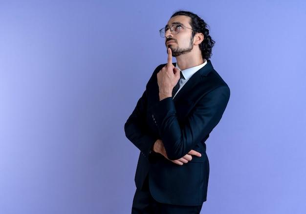 Zakenman in zwart pak en bril kijken verbaasd staande over blauwe muur