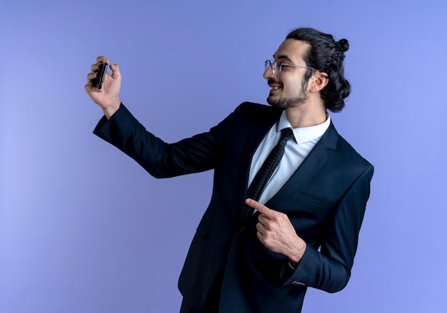 Zakenman in zwart pak en bril met creditcard wijzend met vinger naar de zijkant glimlachend vrolijk staande over blauwe muur