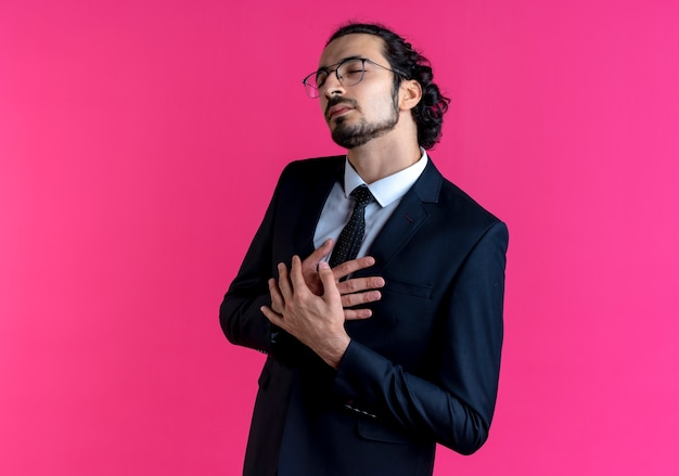 Zakenman in zwart pak en bril met handen gekruist over borst opzij kijken dankbaar gevoel staande over roze muur
