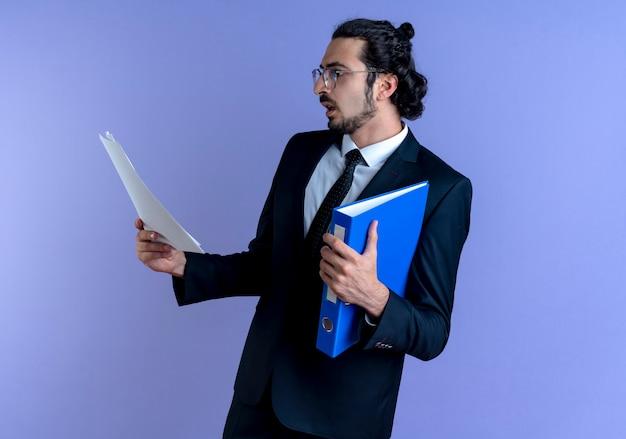 Zakenman in zwart pak en bril met map kijken naar documenten met ernstig gezicht staande over blauwe muur