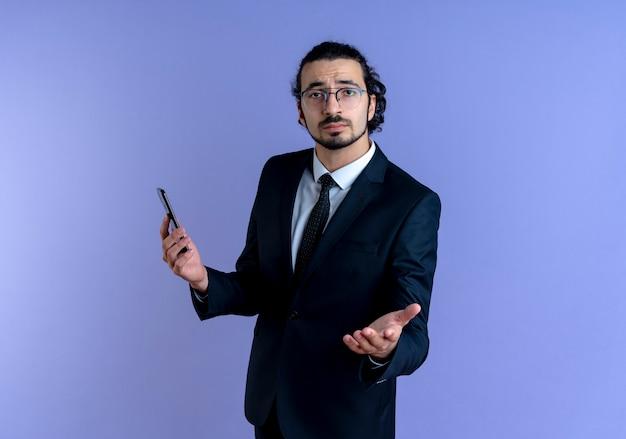 Zakenman in zwart pak en bril met smartphone naar voren kijkend met arm uit als vragen staande over blauwe muur