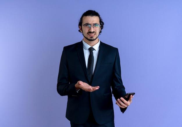 Zakenman in zwart pak en bril met smartphone naar voren kijkend verward en ontevreden staande over blauwe muur