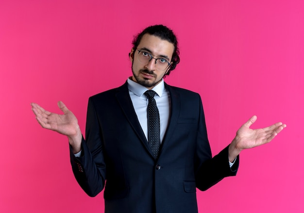 Zakenman in zwart pak en bril naar voren kijken met opgeheven handen met verwarde uitdrukking staande over roze muur