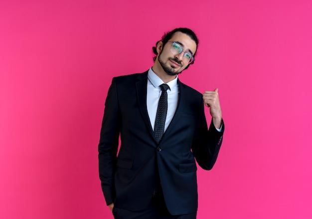 Zakenman in zwart pak en bril naar voren kijken met zelfverzekerde uitdrukking glimlachend wijzend terug staande over roze muur