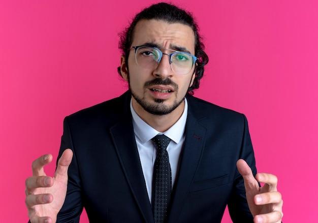 Zakenman in zwart pak en bril naar voren kijkend verward met opgeheven armen die over roze muur staan