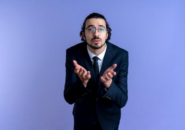 Zakenman in zwart pak en bril op zoek naar de voorkant, blaast een kus hand in hand voor hem staande over blauwe muur