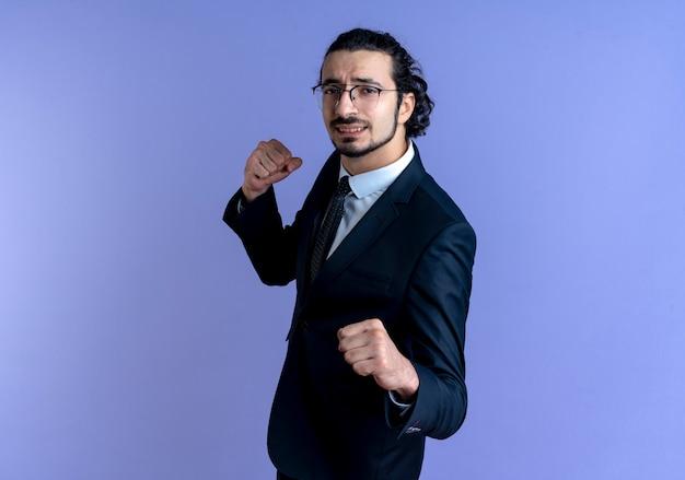 Zakenman in zwart pak en bril op zoek naar de voorkant gebalde vuist die zich voordeed als een bokser die over blauwe muur staat