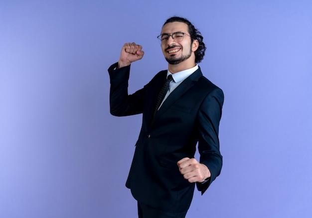 Zakenman in zwart pak en bril op zoek naar de voorkant gebalde vuisten blij en opgewonden staande over blauwe muur