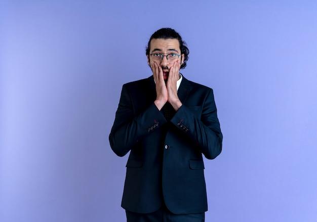 Zakenman in zwart pak en bril op zoek naar de voorkant geschokt bedekkende mond met hand staande over blauwe muur
