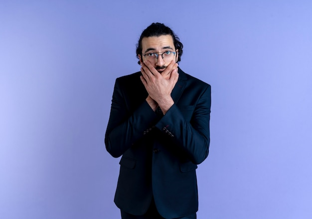Zakenman in zwart pak en bril op zoek naar de voorkant geschokt bedekkende mond met handen die zich over blauwe muur bevinden