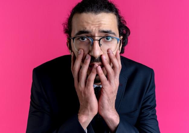 Zakenman in zwart pak en bril op zoek naar de voorkant geschokt bedekkende mond met handen die zich over roze muur bevinden