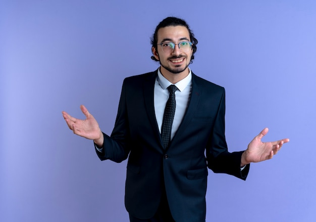 Zakenman in zwart pak en bril op zoek naar de voorkant glimlachend vriendelijk verwelkomend gebaar maken met handen permanent over blauwe muur