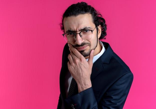 Zakenman in zwart pak en bril op zoek naar de voorkant met hand op kin denken negatieve emoties voelen staande over roze muur