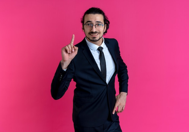Zakenman in zwart pak en bril op zoek naar de voorkant met wijsvinger lachend met geweldig idee staande over roze muur