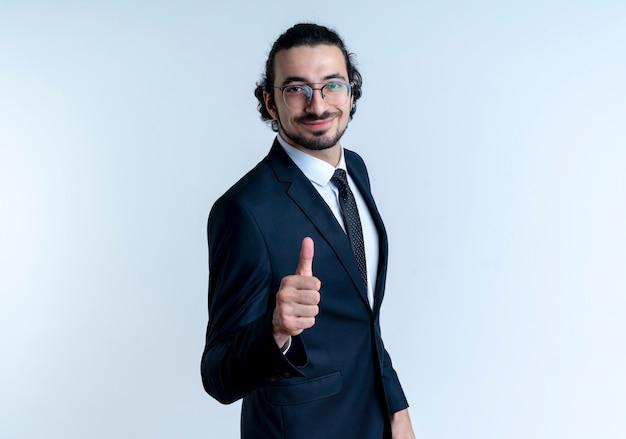 Zakenman in zwart pak en bril op zoek naar de voorkant met zelfverzekerde uitdrukking glimlachend duimen opdagen staande over witte muur