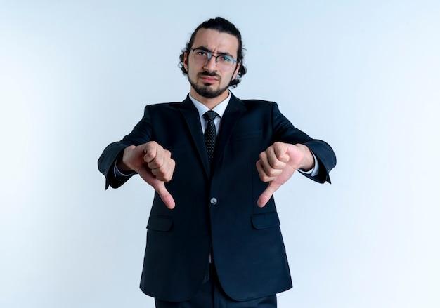 Zakenman in zwart pak en bril op zoek naar de voorkant ontevreden met duimen naar beneden staande over witte muur