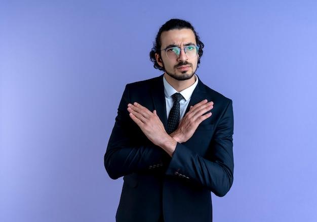 Zakenman in zwart pak en bril op zoek naar de voorkant stopbord kruising handen staande over blauwe muur maken