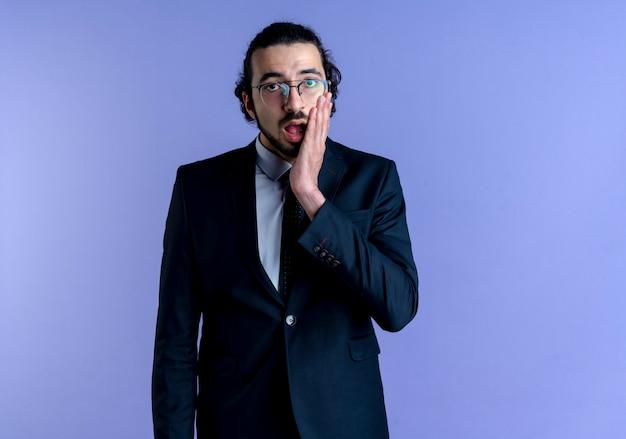 Zakenman in zwart pak en bril op zoek naar de voorkant verrast en verward staande over blauwe muur