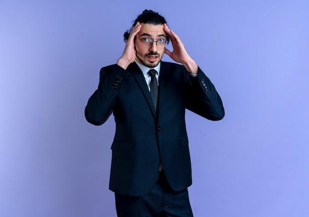 Zakenman in zwart pak en bril op zoek naar de voorkant verward met handen in de buurt van hoofd staande over blauwe muur