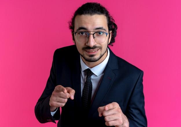 Zakenman in zwart pak en bril op zoek naar voren gebalde vuisten blij en opgewonden staande over roze muur