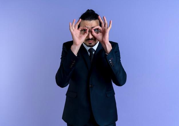 Zakenman in zwart pak en bril verrekijker gebaar met vingers kijken door vingers permanent over blauwe muur