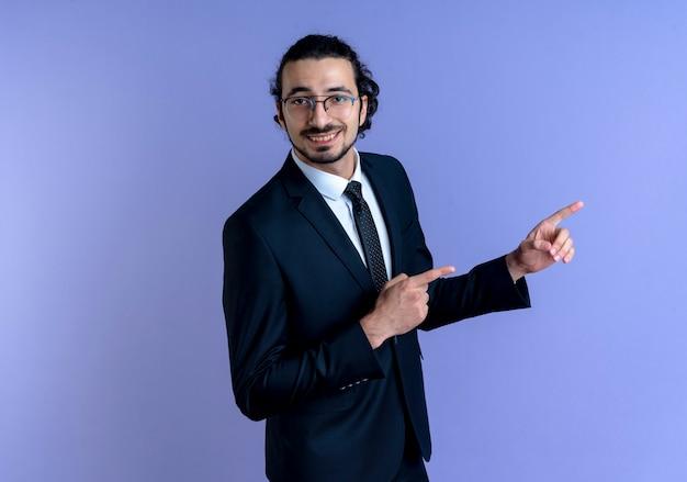 Zakenman in zwart pak en bril wijzend met wijsvingers naar de zijkant glimlachend vrolijk staande over blauwe muur
