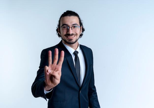 Zakenman in zwart pak en glazen tonen en met vingers omhoog nummer drie glimlachend staande over witte muur