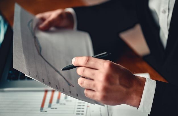 Zakenman in zwart pak maakt aantekeningen over documenten in het kantoor van het businesscentrum.
