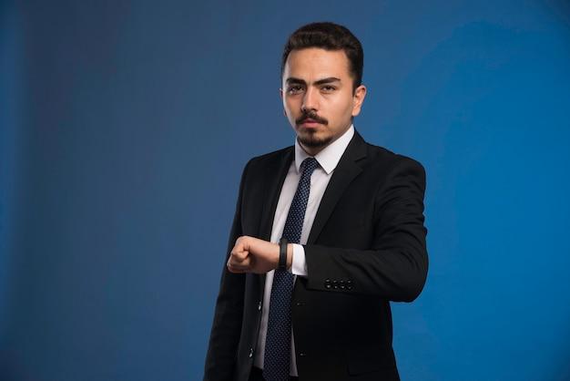 Zakenman in zwart pak met een stropdas die zijn tijd controleert.