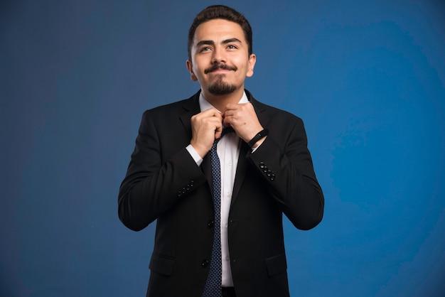 Zakenman in zwart pak openingsknop van zijn overhemd.
